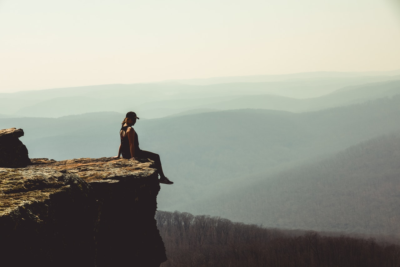 woman-sitting-on-edge-of-rock-formation-1202821.jpg